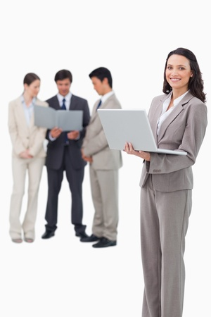 Smiling saleswoman with laptop and associates behind her against a white background photo