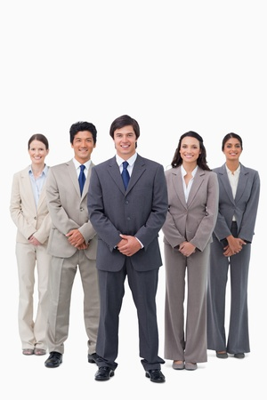 Smiling businessman standing with his team against a white background photo
