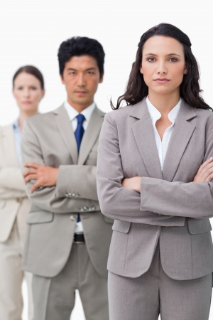 Businesswoman standing with team and folded arms against a white background photo