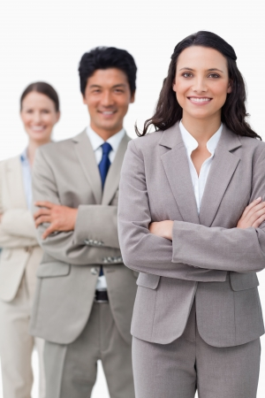 Smiling businesswoman with team and folded arms against a white background photo