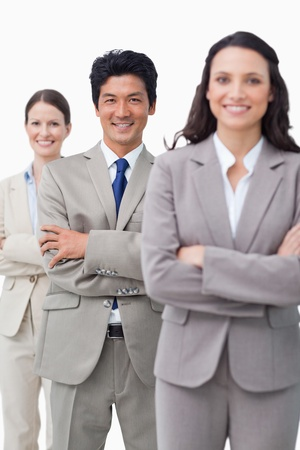Smiling businessteam standing with folded arms against a white background photo