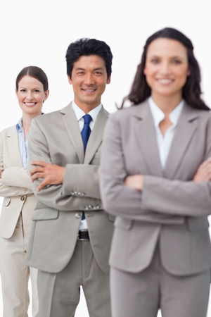 Smiling salesteam standing with folded arms against a white background photo