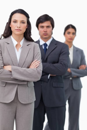 Serious salesteam standing together with folded arms against a white background photo