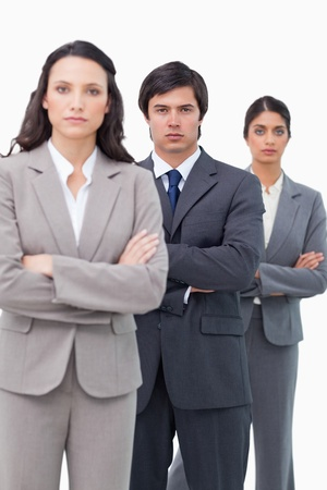 Serious salesteam standing together with arms folded against a white background photo