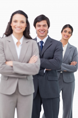 Smiling salesteam standing together with folded arms against a white background photo