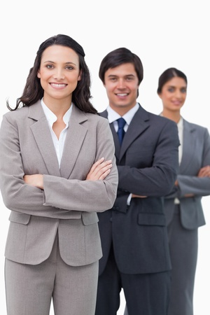 Smiling young saleswoman with her team and arms folded against a white background photo