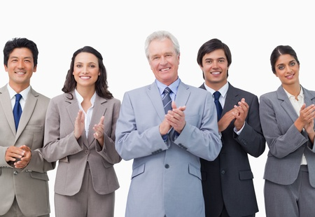 Senior businessman and his team applauding against a white background photo