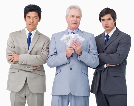 Senior businessman with money standing between his employees against a white background photo