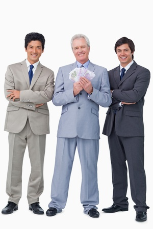 Smiling senior salesman with money and employees against a white background photo