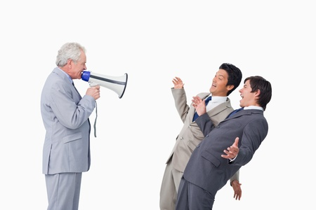 Senior businessman with megaphone yelling at his employees against a white background photo