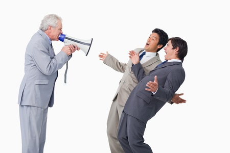 Senior salesman with megaphone yelling at his employees against a white background photo