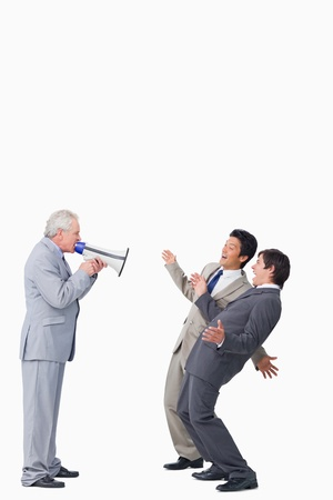 Mature businessman with megaphone yelling at his employees against a white background photo