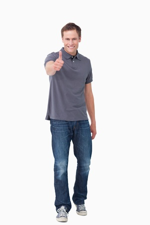 Smiling young man giving thumb up against a white background photo