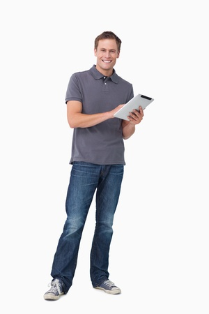 standing man: Smiling young man with his tablet computer against a white background