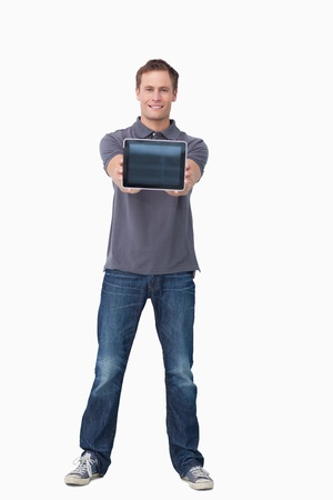 Smiling young man showing screen of tablet computer against a white background photo