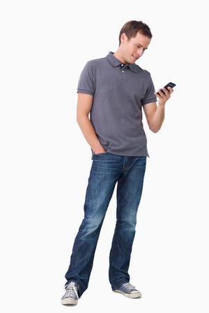 cell phones: Young man typing text message on his cellphone against a white background Stock Photo
