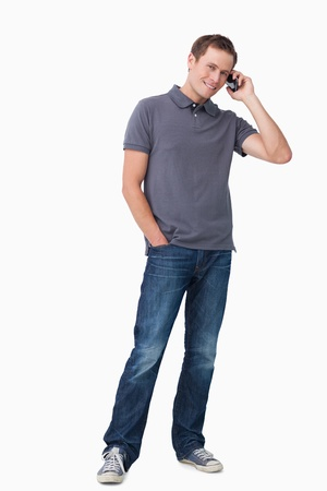 Smiling young man on his cellphone against a white background photo