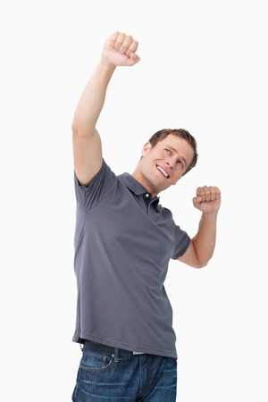 Successful young man celebrating against a white background photo