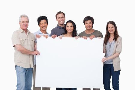 Lachend groep bedrijf blanco teken samen tegen een witte achtergrond Stockfoto