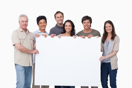 Smiling group holding blank sign together against a white background photo