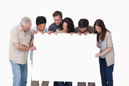 Group looking at blank sign in their hand against a white background photo