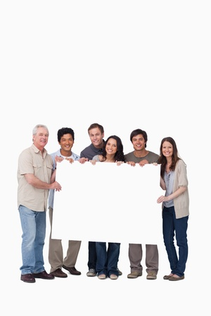 Smiling group of friends holding blank sign together against a white background photo
