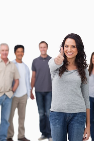 Smiling woman giving thumb up with friends behind her against a white background Stock Photo - 13616200