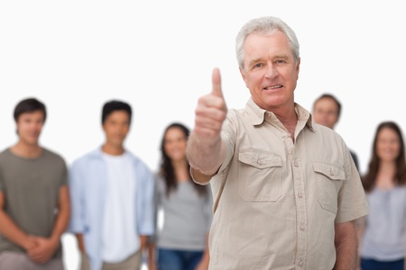 Mature man giving thumb up with young people behind him against a white background photo