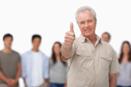 Thumb up given by mature man with young people behind him against a white background photo