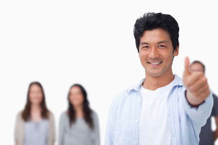 Smiling male with friends behind him giving thump up against a white background photo