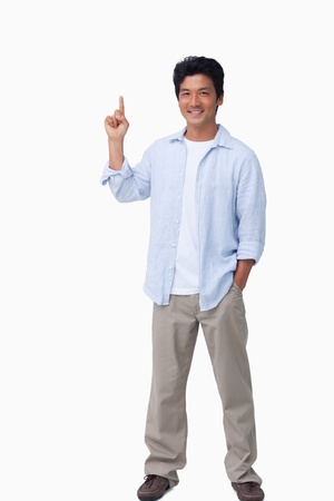 Smiling male pointing up against a white background photo