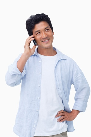 Smiling male on his mobile phone against a white background photo