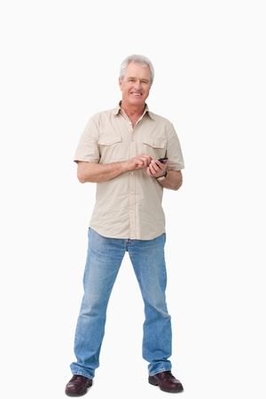 Smiling mature male with his cellphone against a white background photo