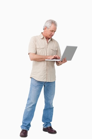 Mature man working on his laptop against a white background photo