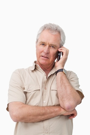 Mature man with his cellphone against a white background photo