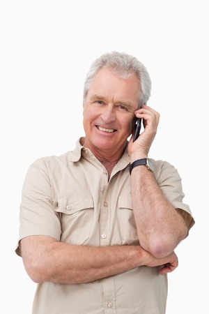 Smiling mature male on his cellphone against a white background photo