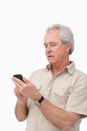 Mature man typing text message on his cellphone against a white background photo