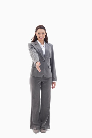 Businesswoman smiling and holding out her hand against white background photo