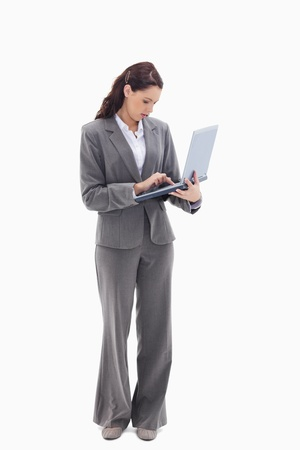 19's: Businesswoman standing and typing on a laptop against white background
