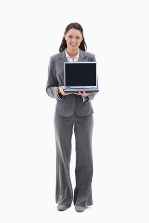 Businesswoman smiling while showing a laptop screen against white background photo