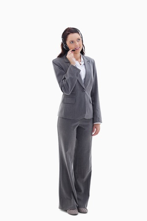 Businesswoman listening with a headset against white background photo