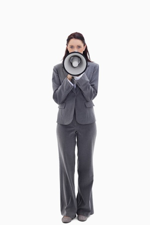 Businesswoman speaking in a megaphone against white background photo