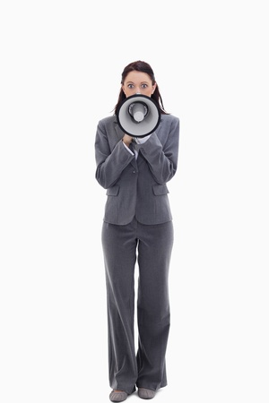 19's: Expressive businesswoman speaking in a megaphone against white background