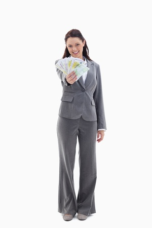 19's: Happy businesswoman with a lot of bank notes in her hand against white background Stock Photo