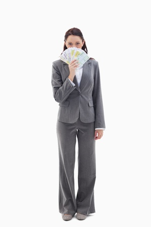 Businesswoman hiding with bank notes in her hand against white background photo
