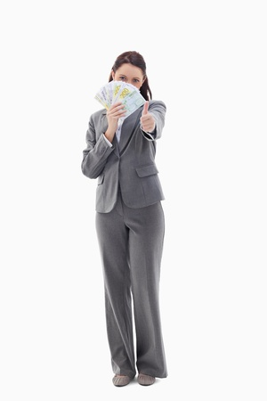 Businesswoman approving and hiding with bank notes in her hand against white background photo