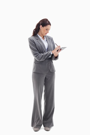 Businesswoman focusing and writing on a clipboard against white background photo