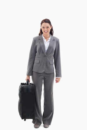 19's: Businesswoman smiling with a suitcase against white background Stock Photo