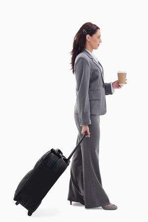 business case: Profiel van een zakenvrouw met een koffer en met een koffie tegen een witte achtergrond