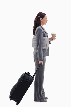 Profile of a businesswoman with a suitcase, a newspaper and a coffee against white background photo